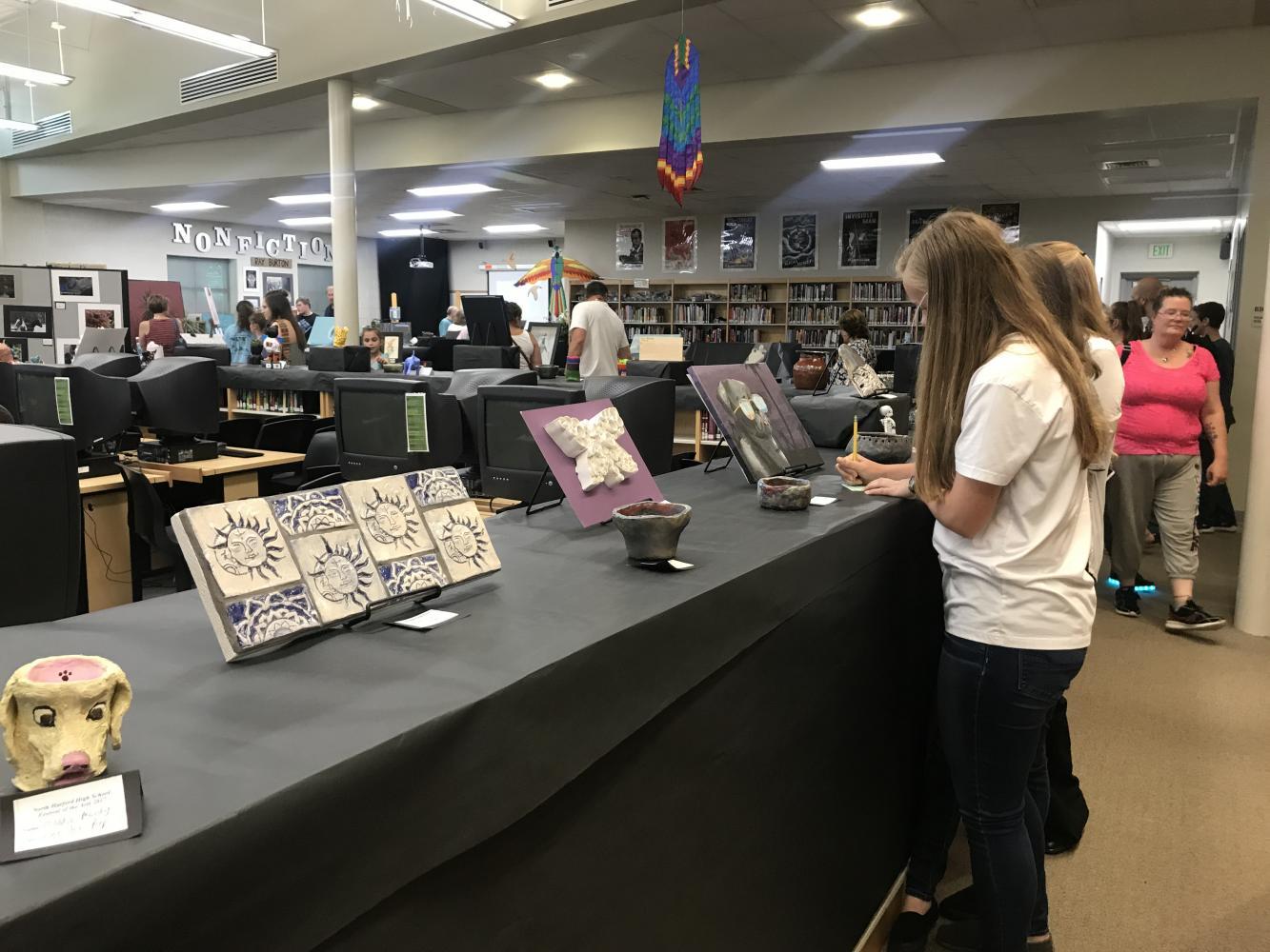 Students gaze at their peers artwork as they visit the displays.