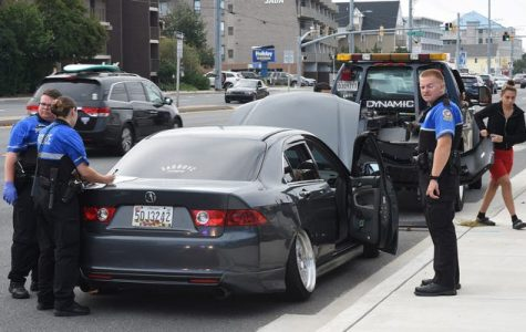 Police search and tow away an illegally modified vehicle. This is just one of the many violations committed by drivers during the event.