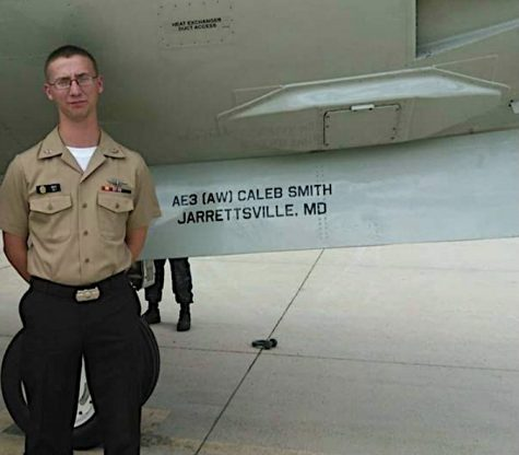 North Harford alumnus Caleb Smith, now an aviation electrician in the United States Navy standing next to plane as Plane Captain Photo credit: Caleb Smith